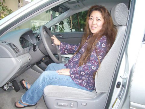Kimberly in her car, using the pedal extenders